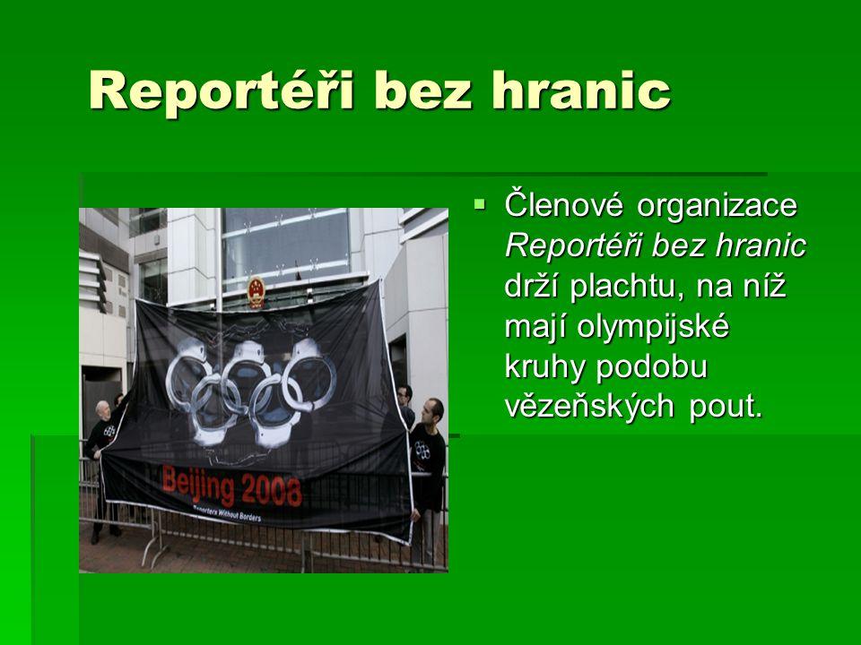Reportéři bez hranic Reportéři bez hranic  Členové organizace Reportéři bez hranic drží plachtu, na níž mají olympijské kruhy podobu vězeňských pout.
