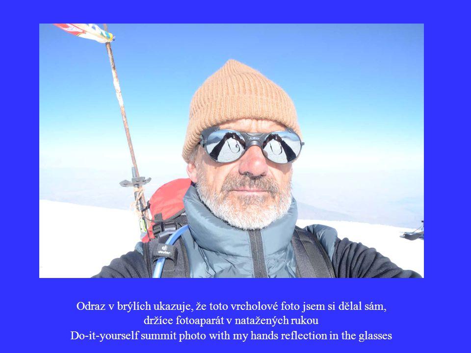 Odraz v brýlích ukazuje, že toto vrcholové foto jsem si dělal sám, držíce fotoaparát v natažených rukou Do-it-yourself summit photo with my hands reflection in the glasses