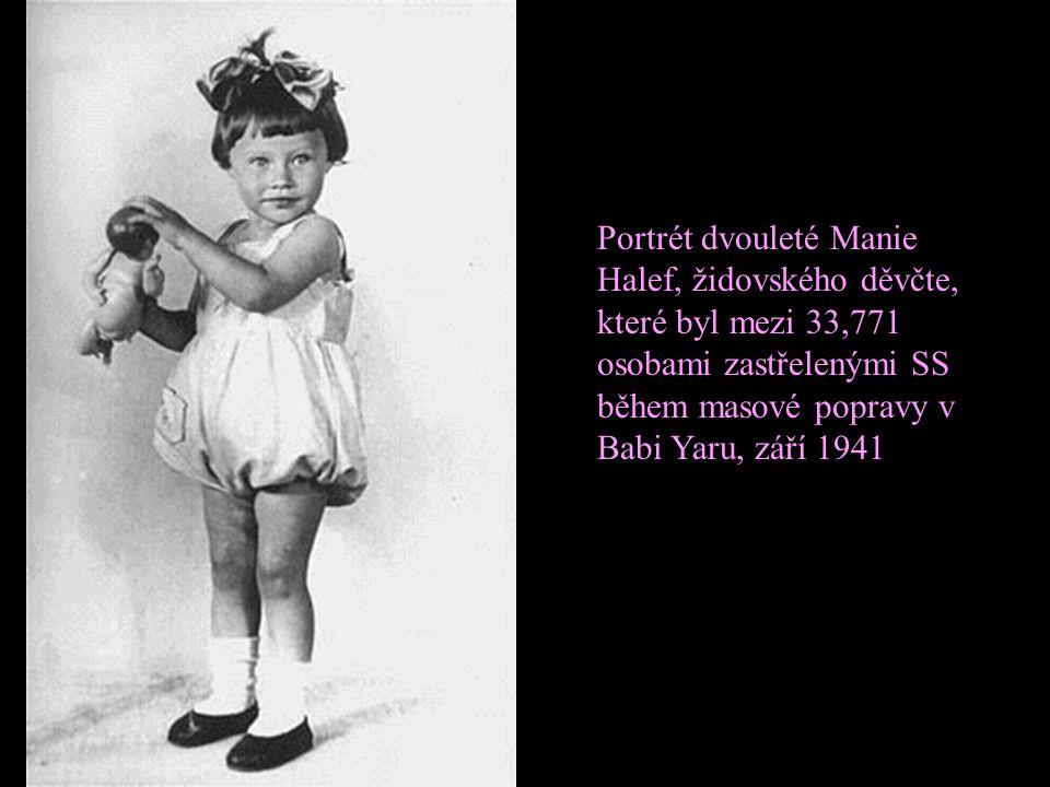Příslušník SS střílí jednotlivě židovské ženy, které zůstaly načivu v rokli po hromadné popravě.