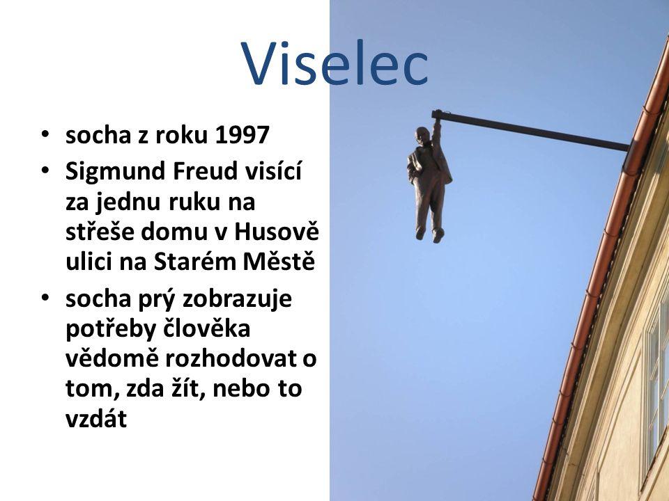 Viselec socha z roku 1997 Sigmund Freud visící za jednu ruku na střeše domu v Husově ulici na Starém Městě socha prý zobrazuje potřeby člověka vědomě