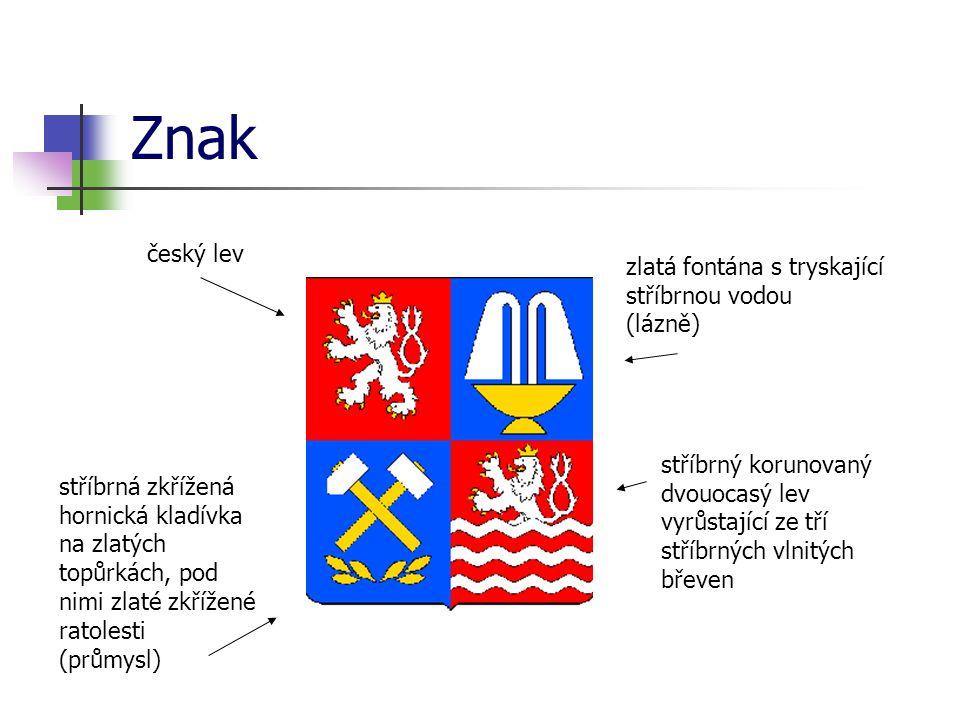 Znak český lev zlatá fontána s tryskající stříbrnou vodou (lázně) stříbrná zkřížená hornická kladívka na zlatých topůrkách, pod nimi zlaté zkřížené ra