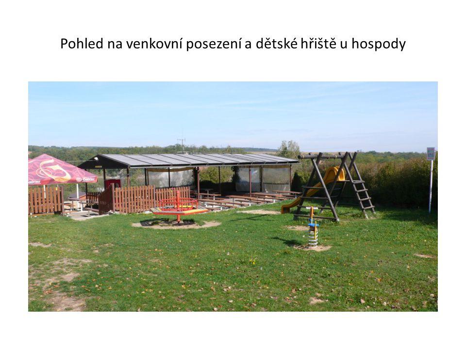 Pohled na venkovní posezení a dětské hřiště u hospody