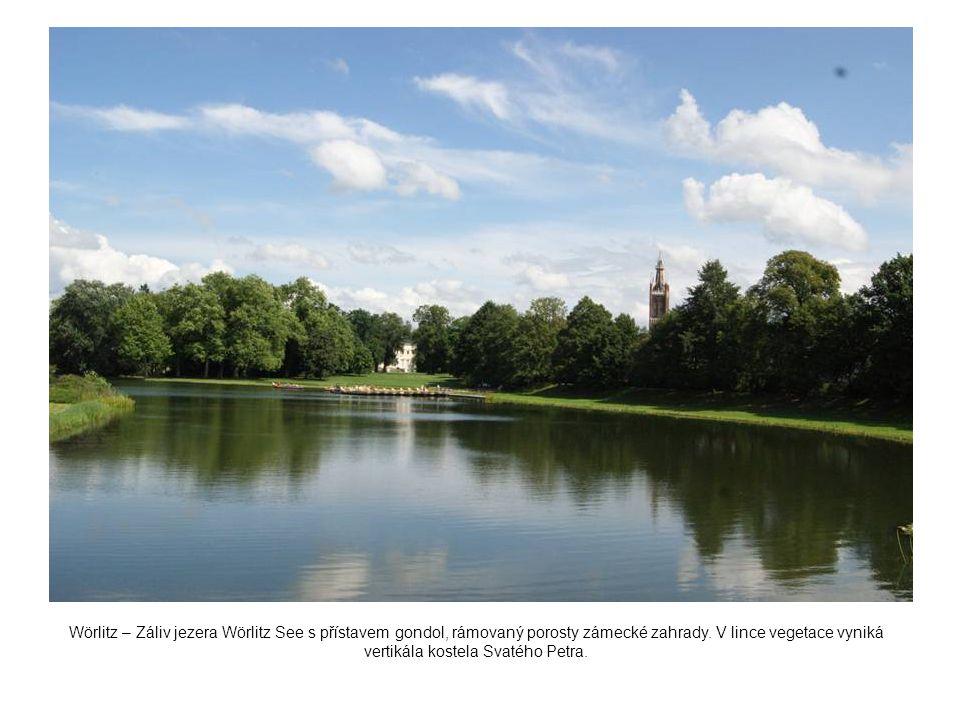 Wörlitz – Záliv jezera Wörlitz See s přístavem gondol, rámovaný porosty zámecké zahrady. V lince vegetace vyniká vertikála kostela Svatého Petra.