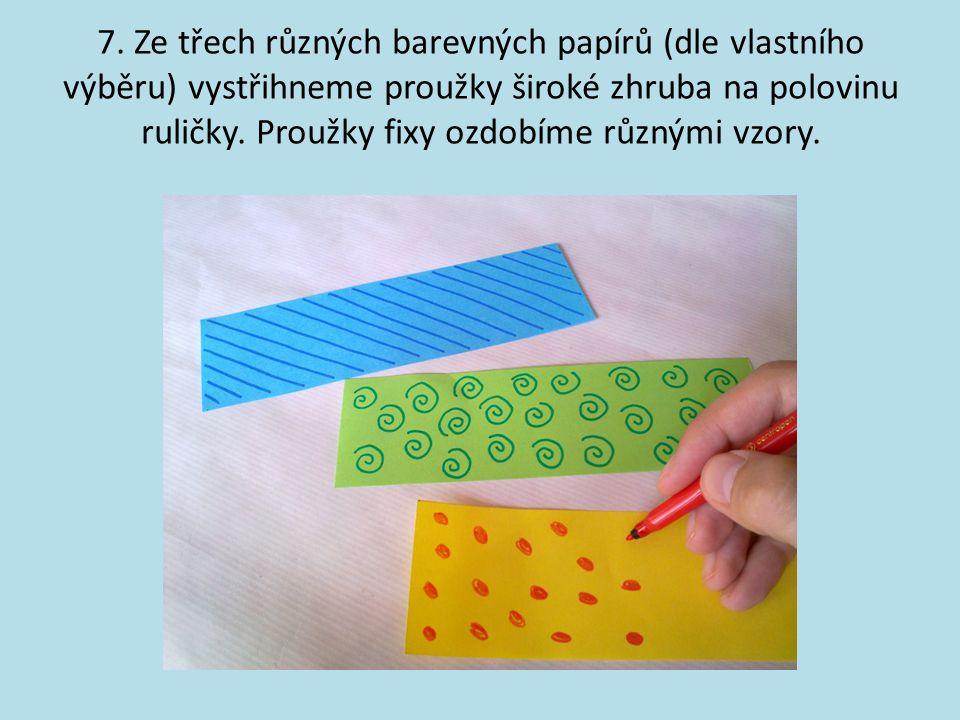 7. Ze třech různých barevných papírů (dle vlastního výběru) vystřihneme proužky široké zhruba na polovinu ruličky. Proužky fixy ozdobíme různými vzory