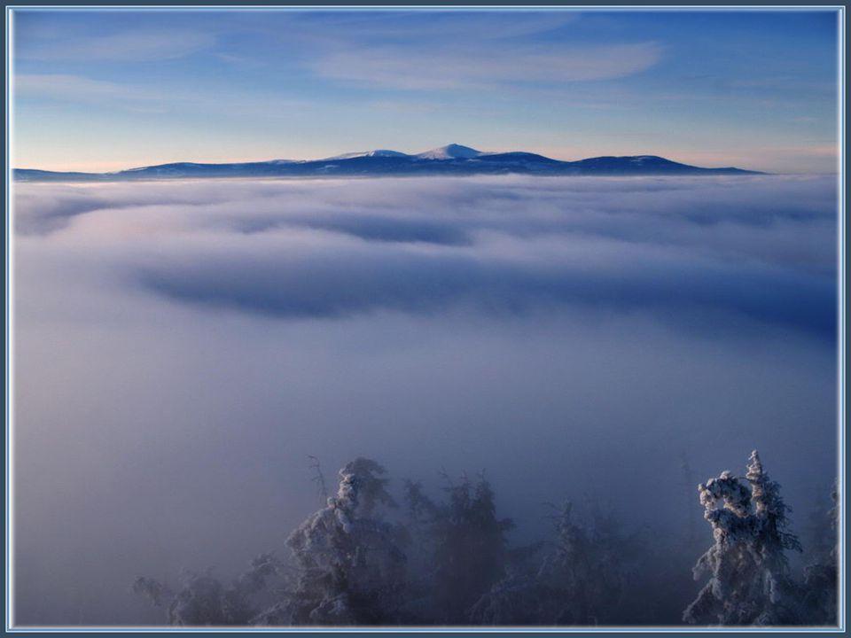 Mlha se valila přes hřebeny a paprsky slunce každou chvíli měnily její barvu.