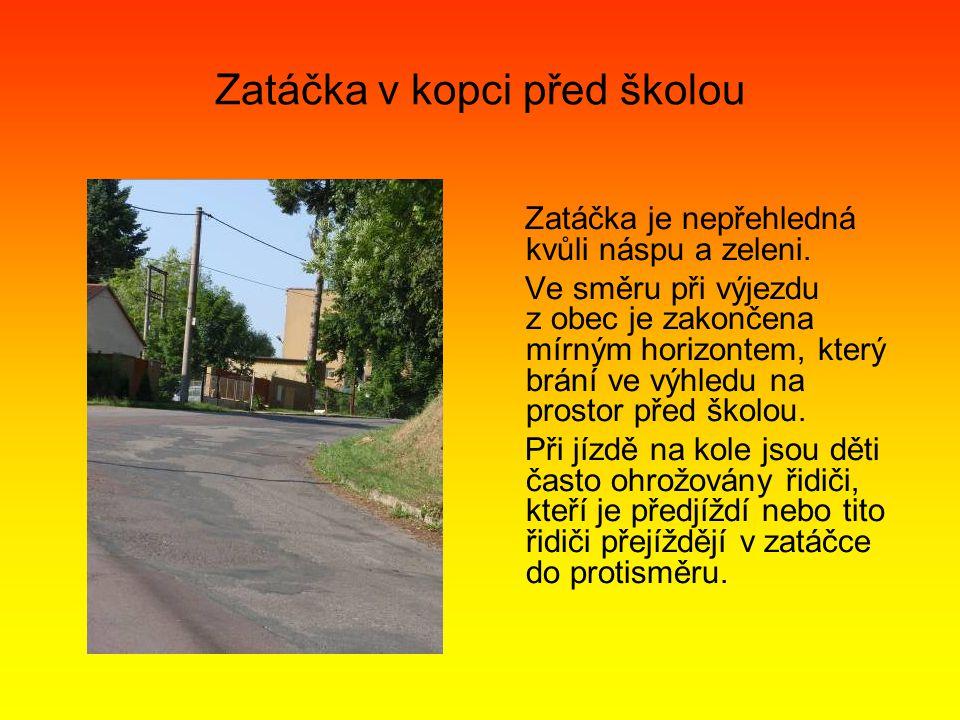 Zatáčka v kopci před školou Zatáčka je nepřehledná kvůli náspu a zeleni.