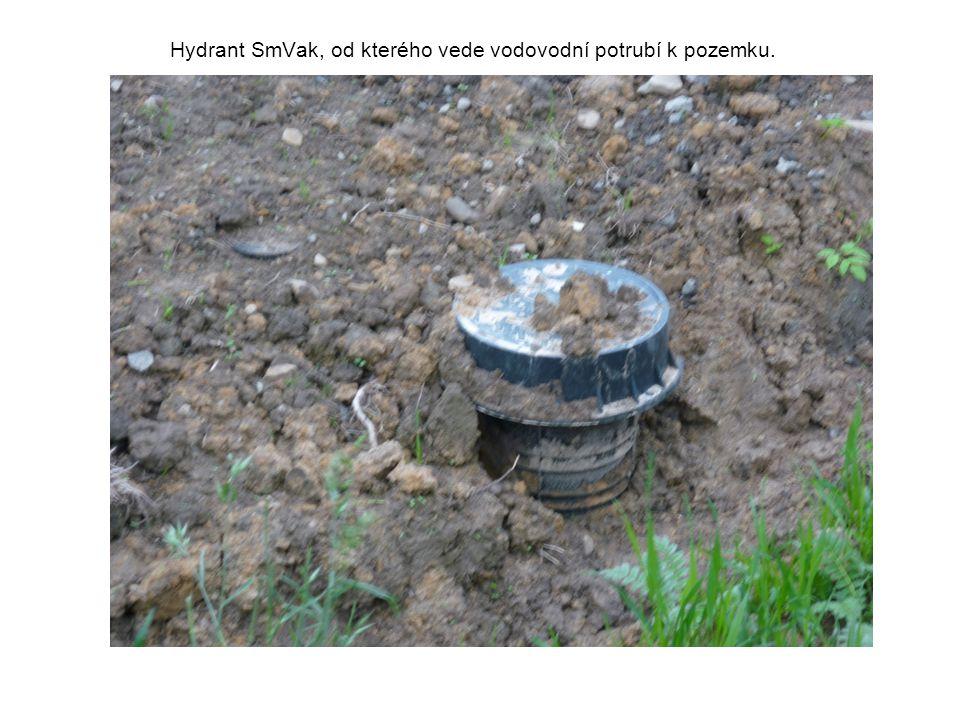 Hydrant SmVak, od kterého vede vodovodní potrubí k pozemku.