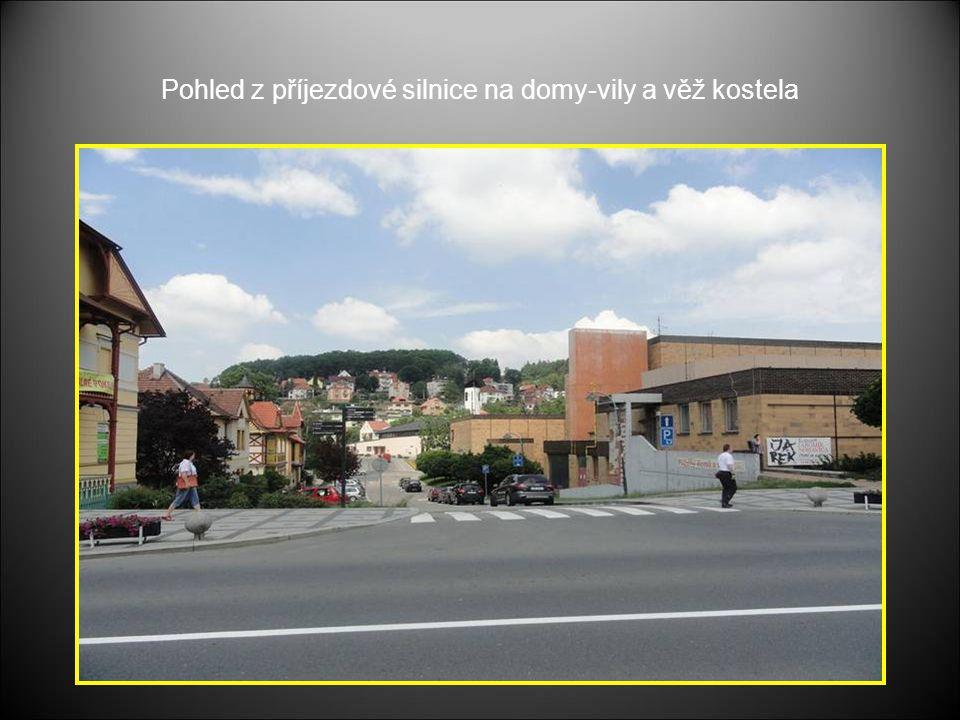 Pohled z příjezdové silnice na domy-vily a věž kostela