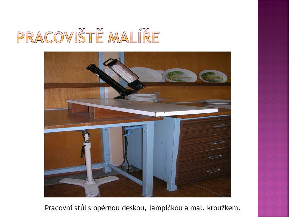 Pracovní stůl s opěrnou deskou, lampičkou a mal. kroužkem.