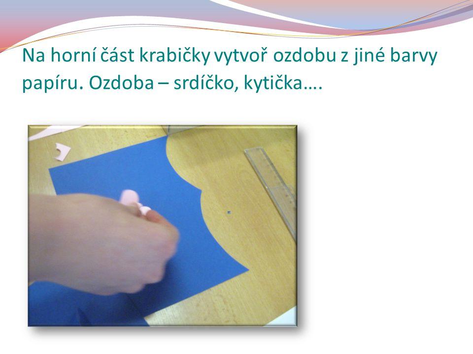 Na horní část krabičky vytvoř ozdobu z jiné barvy papíru. Ozdoba – srdíčko, kytička….