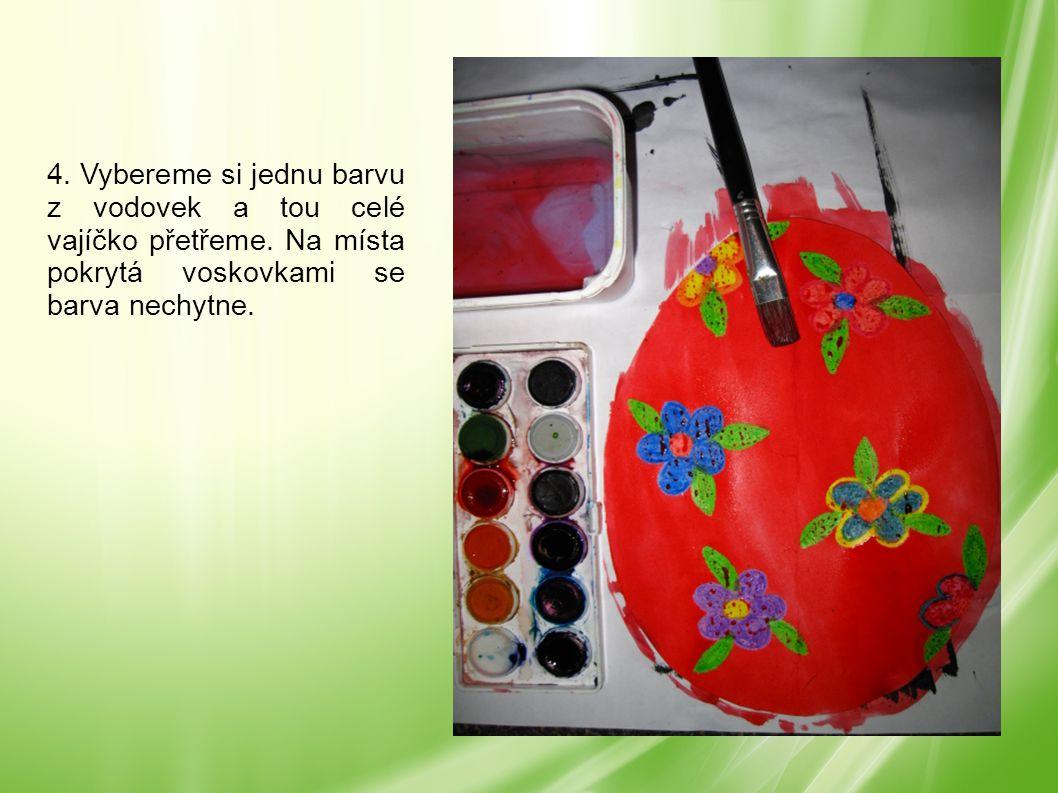 4. Vybereme si jednu barvu z vodovek a tou celé vajíčko přetřeme. Na místa pokrytá voskovkami se barva nechytne.