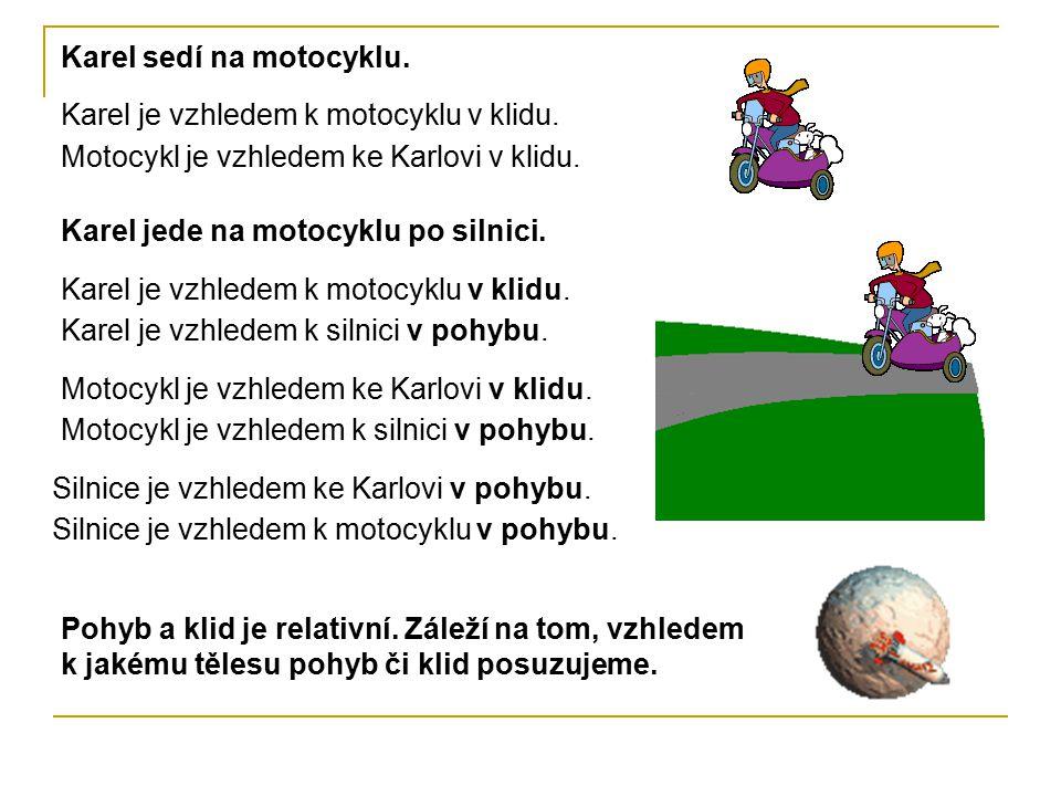 Karel je vzhledem k motocyklu v klidu. Karel sedí na motocyklu. Motocykl je vzhledem ke Karlovi v klidu. Karel je vzhledem k motocyklu v klidu. Karel