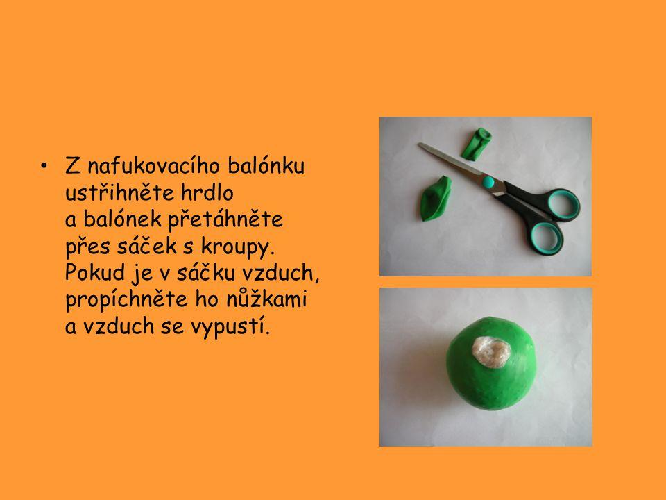 Z nafukovacího balónku ustřihněte hrdlo a balónek přetáhněte přes sáček s kroupy. Pokud je v sáčku vzduch, propíchněte ho nůžkami a vzduch se vypustí.