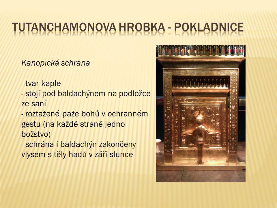 Kanopická schrána - tvar kaple - stojí pod baldachýnem na podložce ze saní - roztažené paže bohů v ochranném gestu (na každé straně jedno božstvo) - s