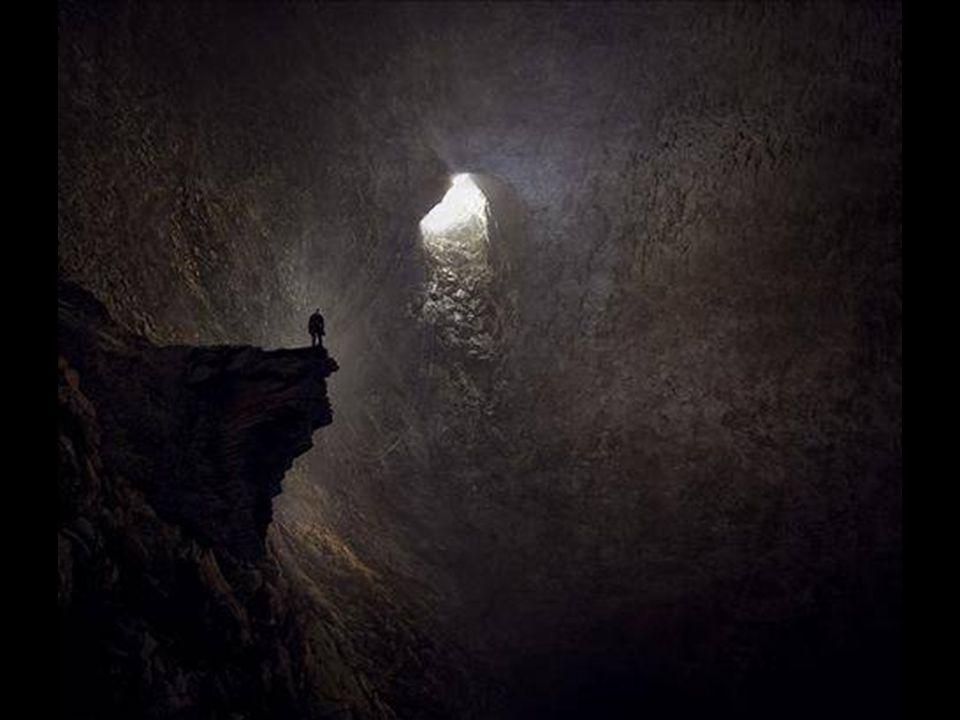 Obrovský sluneční paprsek proniká do jeskyně jako vodopád. V popředí je obrovský stalagmit a průzkumník.
