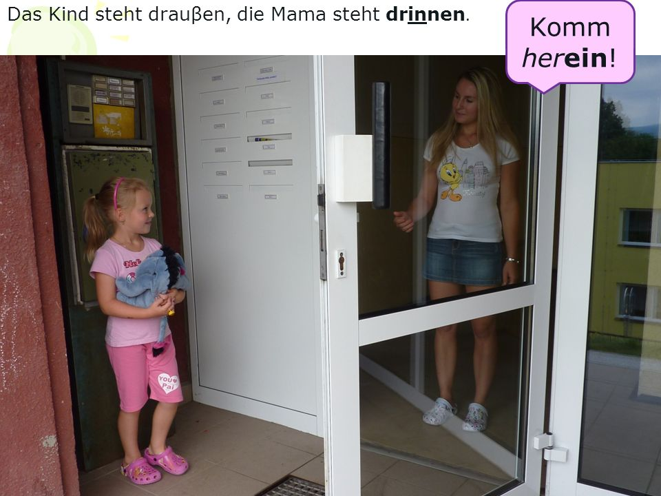 Das Kind steht drauβen, die Mama steht drinnen. Komm herein!
