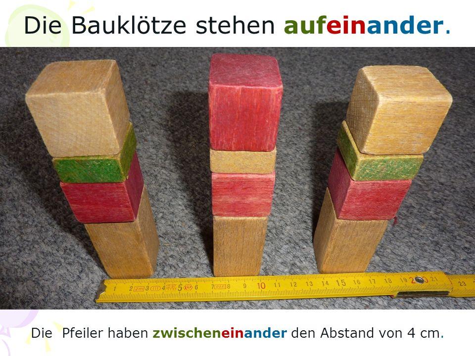 Die Bauklötze stehen aufeinander. Die Pfeiler haben zwischeneinander den Abstand von 4 cm.