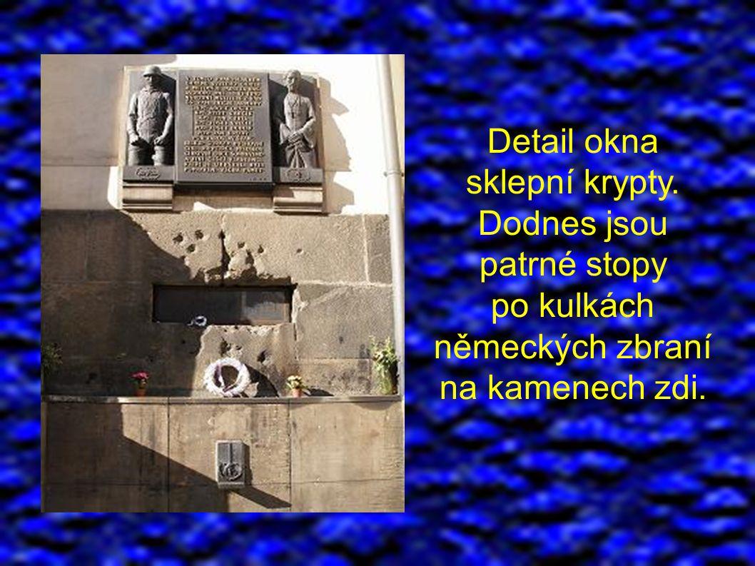 Detail okna sklepní krypty. Dodnes jsou patrné stopy po kulkách německých zbraní na kamenech zdi.