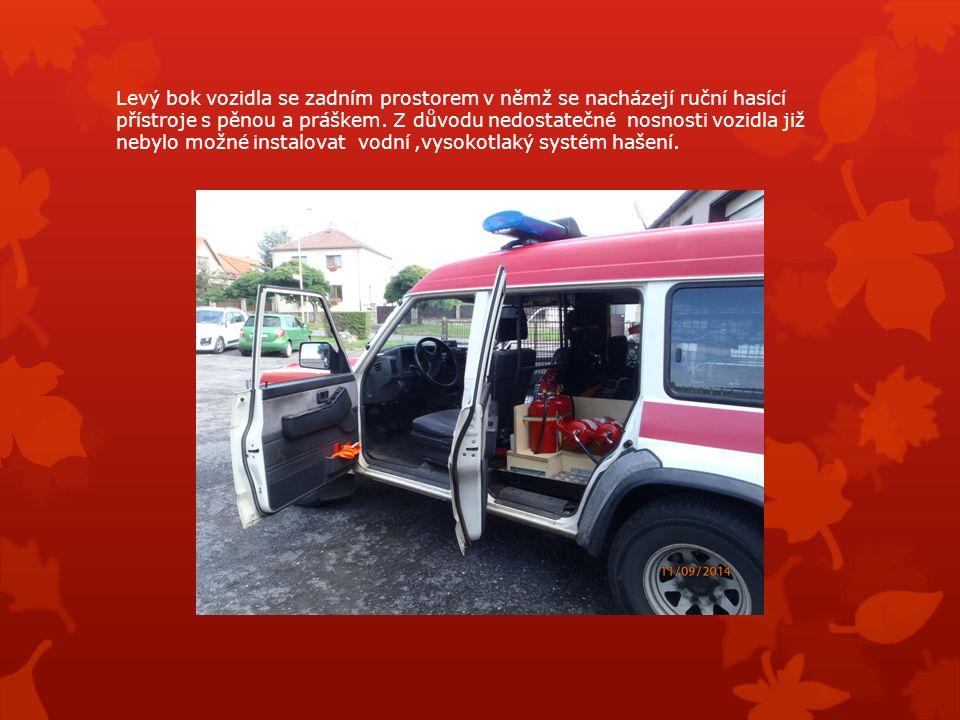 Levý bok vozidla se zadním prostorem v němž se nacházejí ruční hasící přístroje s pěnou a práškem.