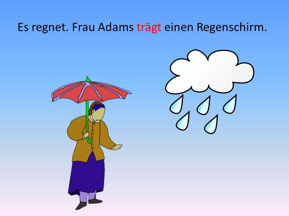 Es regnet. Frau Adams trägt einen Regenschirm.