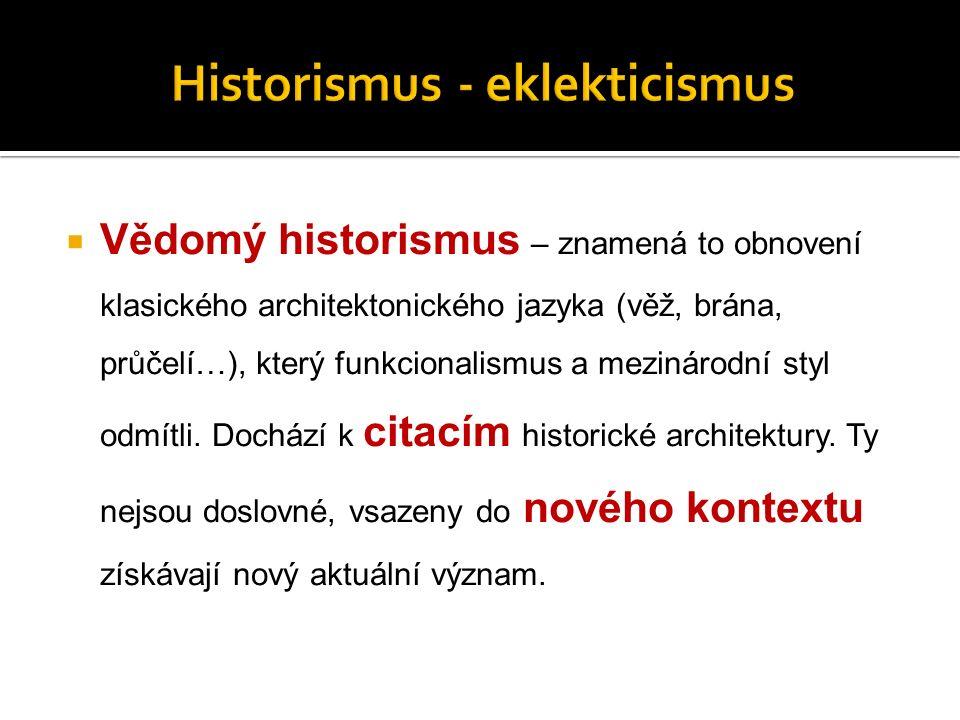  Vědomý historismus – znamená to obnovení klasického architektonického jazyka (věž, brána, průčelí…), který funkcionalismus a mezinárodní styl odmítli.