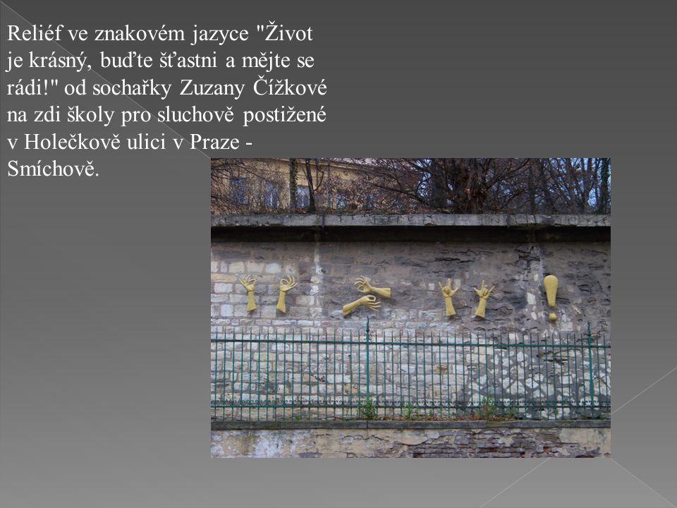 Reliéf ve znakovém jazyce Život je krásný, buďte šťastni a mějte se rádi! od sochařky Zuzany Čížkové na zdi školy pro sluchově postižené v Holečkově ulici v Praze - Smíchově.