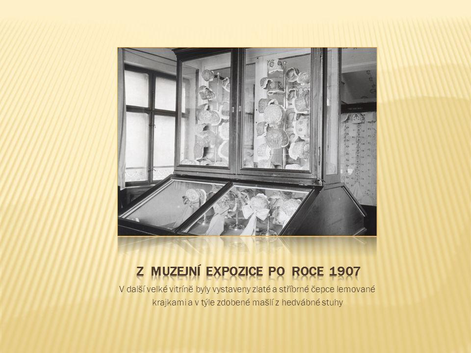 V další velké vitríně byly vystaveny zlaté a stříbrné čepce lemované krajkami a v týle zdobené mašlí z hedvábné stuhy