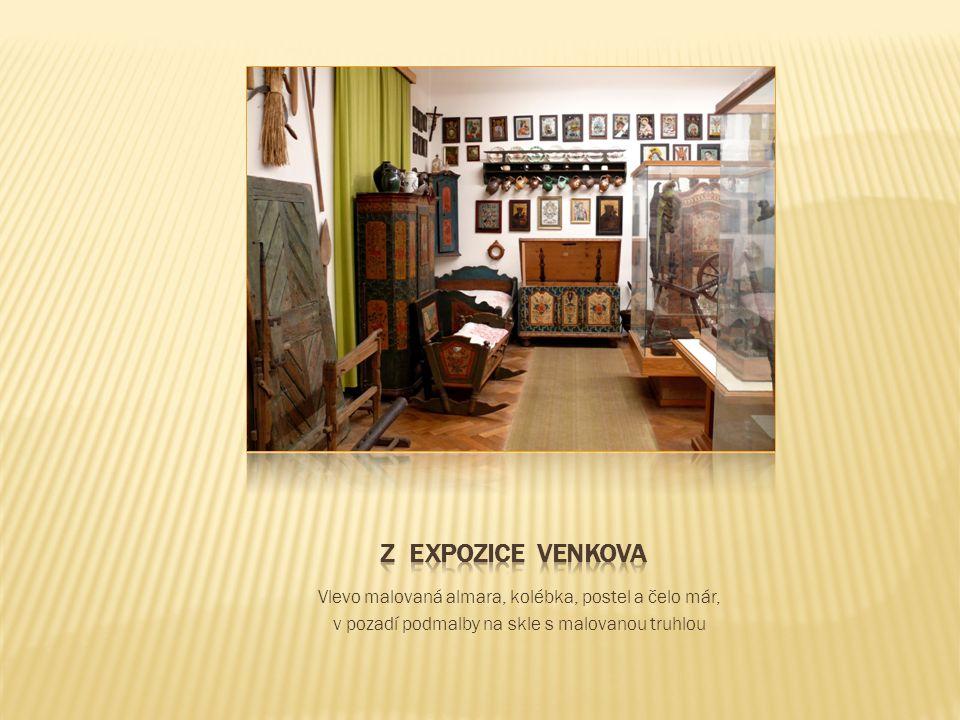 Vlevo malovaná almara, kolébka, postel a čelo már, v pozadí podmalby na skle s malovanou truhlou