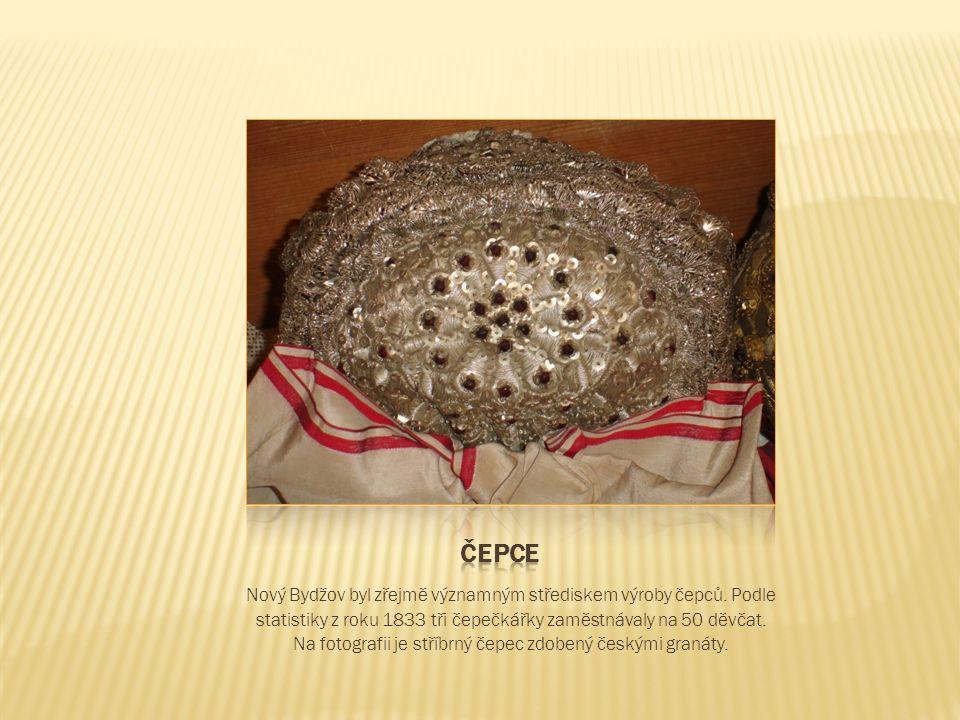Bohatou reliéfní výzdobu ze stříbrného a zlaceného dracounu doplňují české granáty a flitry (penízky)