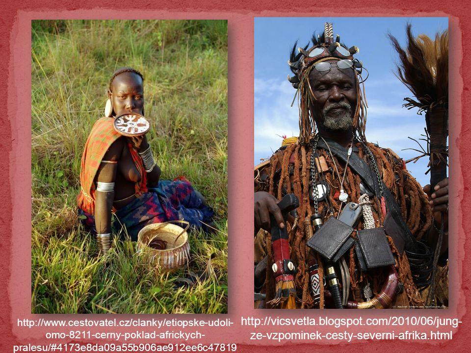 Africké bubny a plápolající oheň.Kolem ohně poskakují afričtí domorodci v maskách nebo s oštěpy.