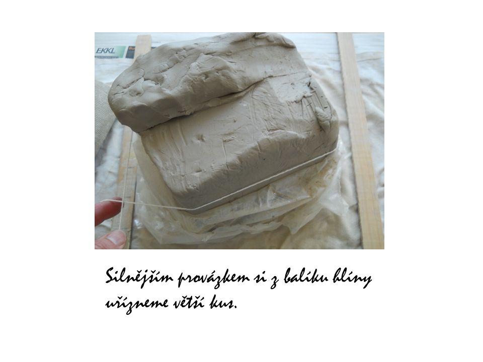 Silnějším provázkem si z balíku hlíny uřízneme větší kus.