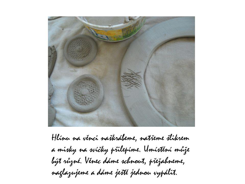 Hlínu na věnci naškrábeme, natřeme šlikrem a misky na svíčky přilepíme.