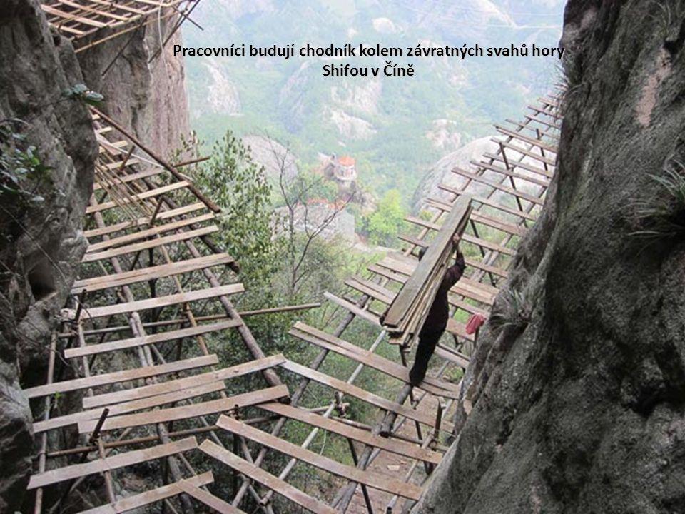 Pracovníci budují chodník kolem závratných svahů hory Shifou v Číně
