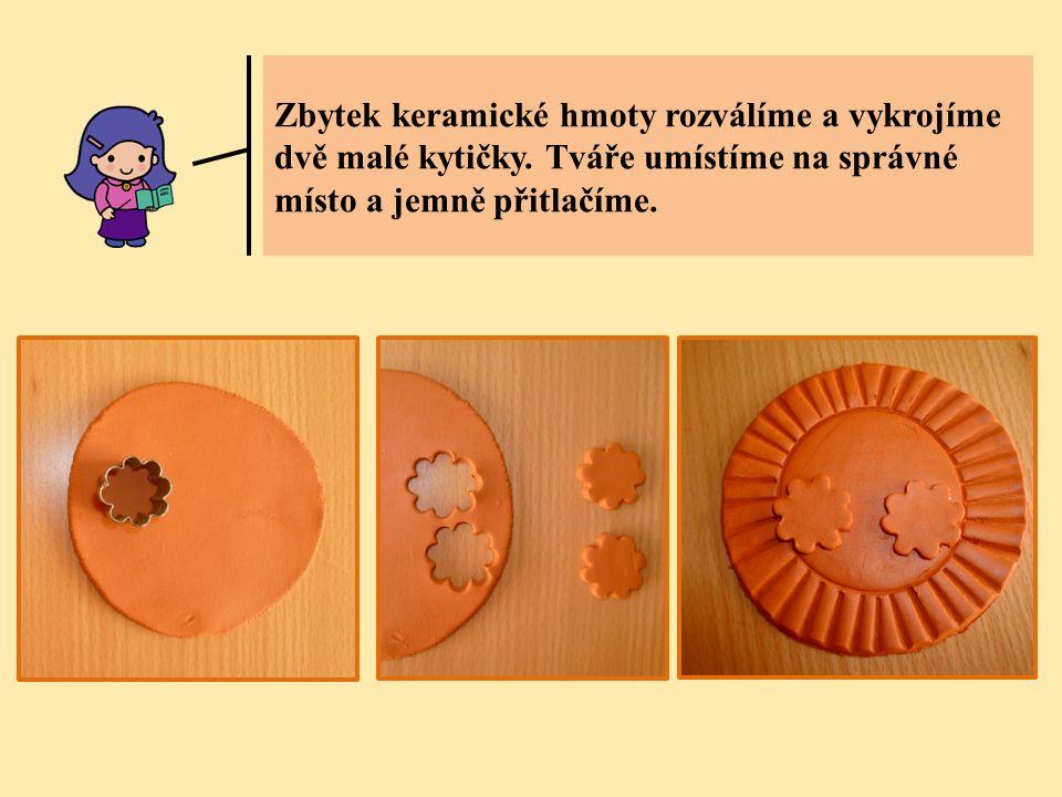 Zbytek keramické hmoty rozválíme a vykrojíme dvě malé kytičky. Tváře umístíme na správné místo a jemně přitlačíme.