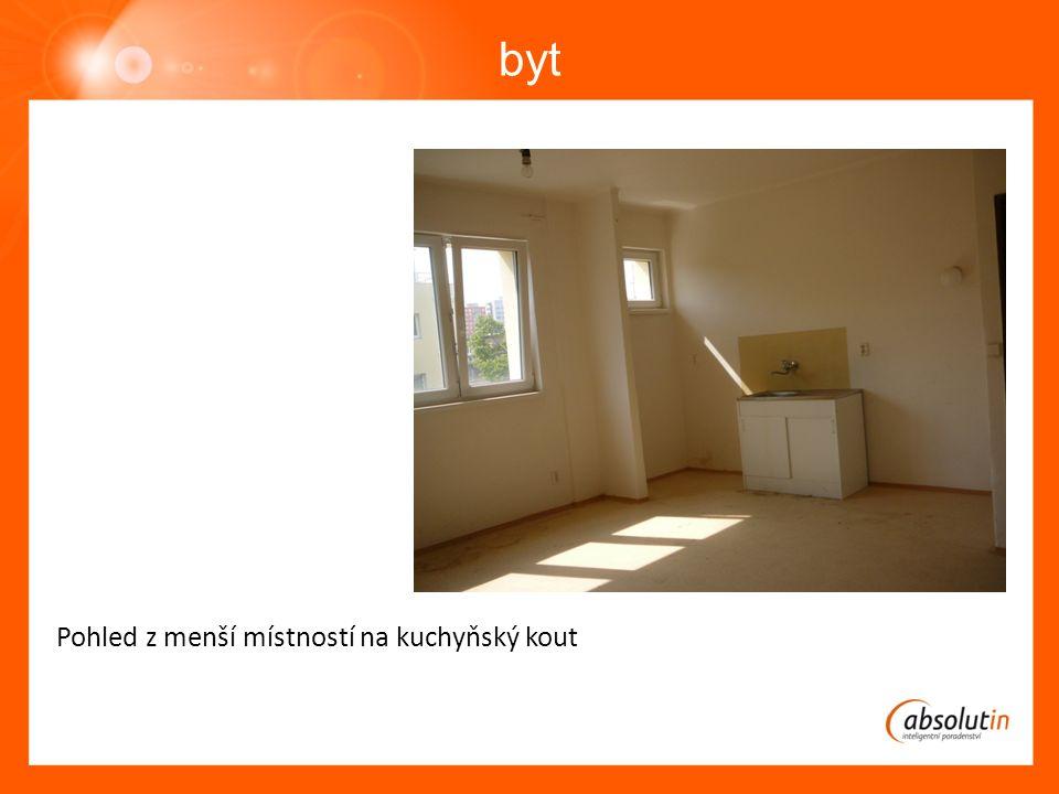 byt Pohled z menší místností na kuchyňský kout