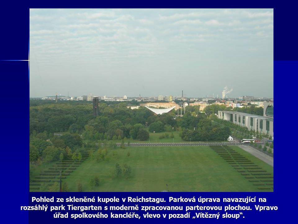 Pohled ze skleněné kupole v Reichstagu. Parková úprava navazující na rozsáhlý park Tiergarten s moderně zpracovanou parterovou plochou. Vpravo úřad sp