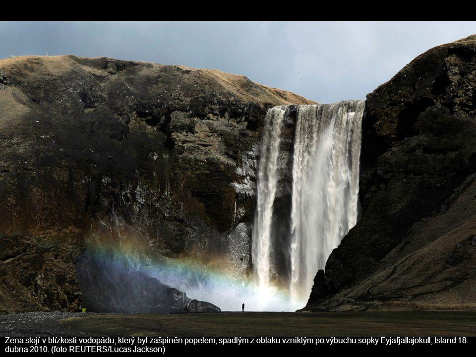Žena stojí v blízkosti vodopádu, který byl zašpiněn popelem, spadlým z oblaku vzniklým po výbuchu sopky Eyjafjallajokull, Island 18. dubna 2010. (foto