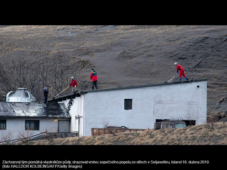 Záchranný tým pomáhá vlastníkům půdy, shazovat vrstvu sopečného popelu ze střech v Seljavelliru, Island 18. dubna 2010. (foto HALLDOR KOLBEINS/AFP/Get