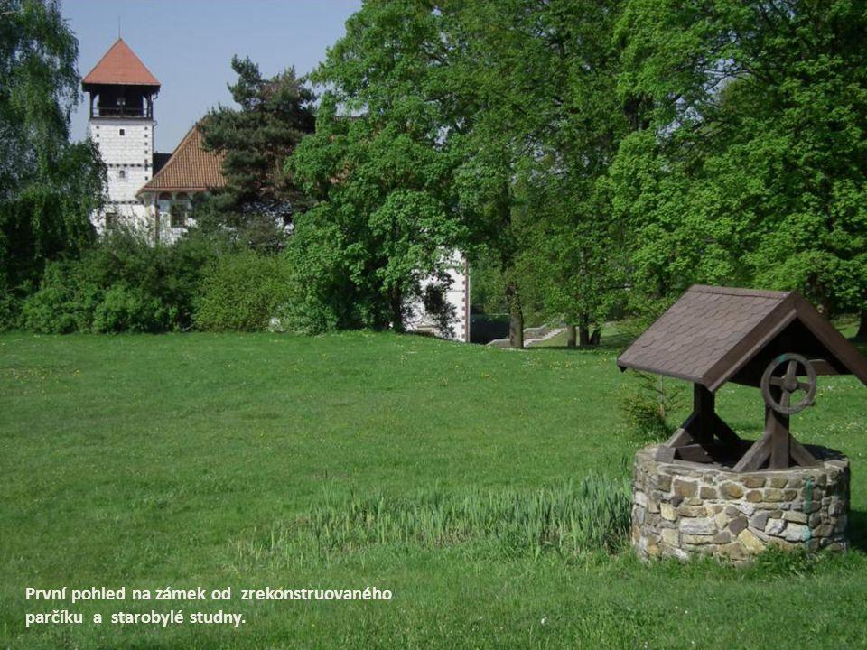 První pohled na zámek od zrekonstruovaného parčíku a starobylé studny.