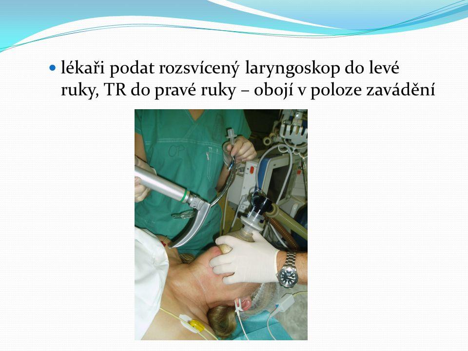  lékaři podat rozsvícený laryngoskop do levé ruky, TR do pravé ruky – obojí v poloze zavádění