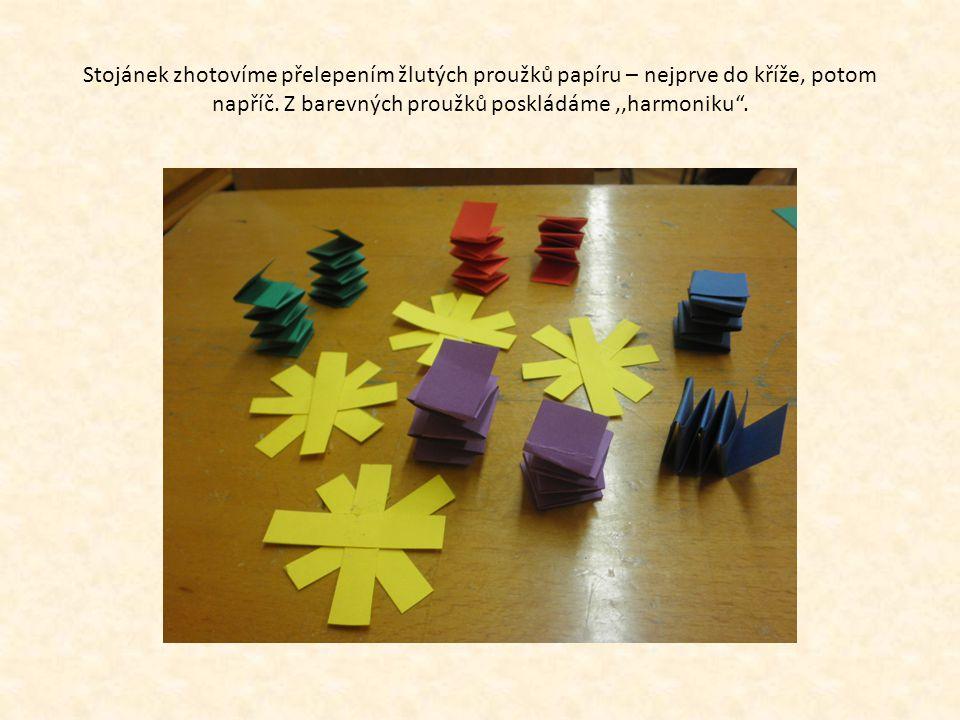 """Stojánek zhotovíme přelepením žlutých proužků papíru – nejprve do kříže, potom napříč. Z barevných proužků poskládáme,,harmoniku""""."""