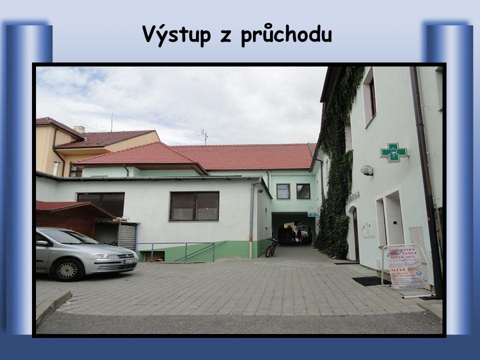 Budova s obchodem a restaurací ve, které je průchod z náměstí