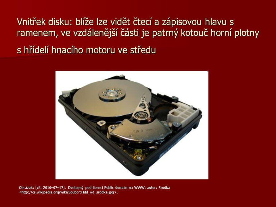 Vnitřek disku: blíže lze vidět čtecí a zápisovou hlavu s ramenem, ve vzdálenější části je patrný kotouč horní plotny s hřídelí hnacího motoru ve střed