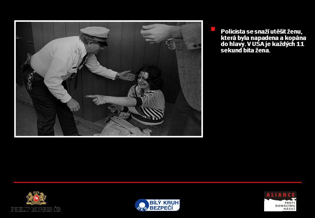  Policista se snaží utěšit ženu, která byla napadena a kopána do hlavy. V USA je každých 11 sekund bita žena.