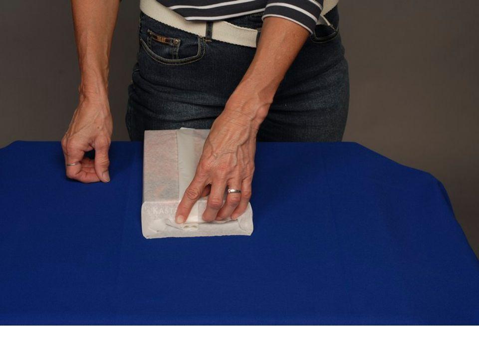 7.Otočíme bonboniéru o 90° a prsty obou rukou přitiskneme papír k boční stěně bonboniéry směrem dolů