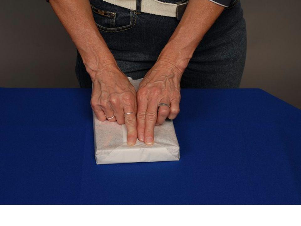 10.Zbývající část papíru přitiskneme k boční stěně bonboniéry směrem nahoru a prsty vyznačíme hranu, která určuje výšku bonboniéry.