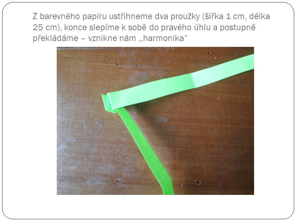 Z barevného papíru ustřihneme dva proužky (šířka 1 cm, délka 25 cm), konce slepíme k sobě do pravého úhlu a postupně překládáme – vznikne nám,,harmonika