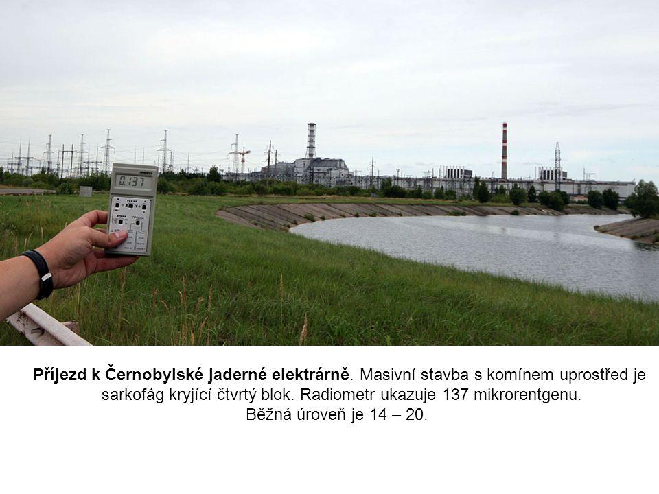 Příjezd k Černobylské jaderné elektrárně. Masivní stavba s komínem uprostřed je sarkofág kryjící čtvrtý blok. Radiometr ukazuje 137 mikrorentgenu. Běž